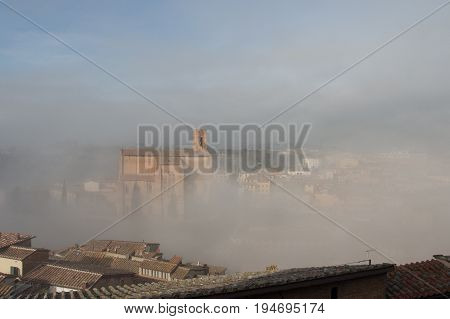 Italy Siena - December 26 2016: the view of Basilica Cateriniana of San Domenico in the thick fog on December 26 2016 in Siena Tuscany Italy.