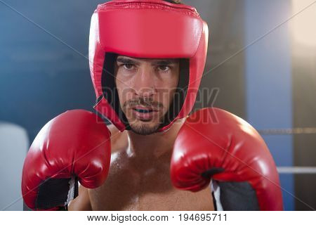 Close-up portrait of confident male boxer wearing red headgear and gloves in boxing ring