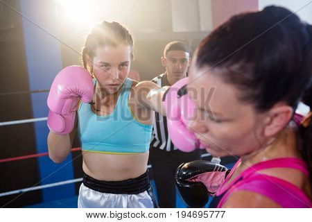 Referee looking at female boxers fighting in boxing ring at fitness studio