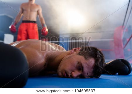 Unconscious male boxer lying by athlete in boxing ring at fitness studio