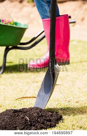 Low section of woman in rubber boot with shovel at lawn on sunny day