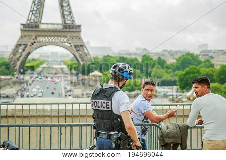PARIS, FRANCE - JUNE 30, 2017: Police officers patrolling the tourists at Palais de Chaillot palace with Paris Eiffel Tower. The Tour Eiffel is icon of Paris.