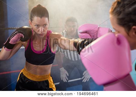 Female athletes fighting while referee looking in boxing ring at fitness studio
