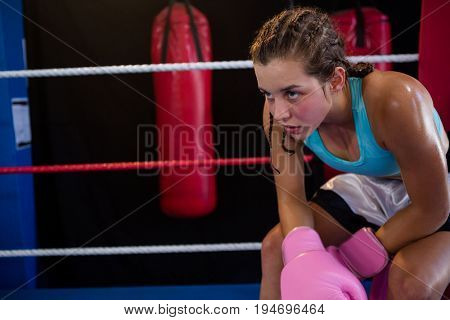 Tired young boxer sitting at corner in boxing ring