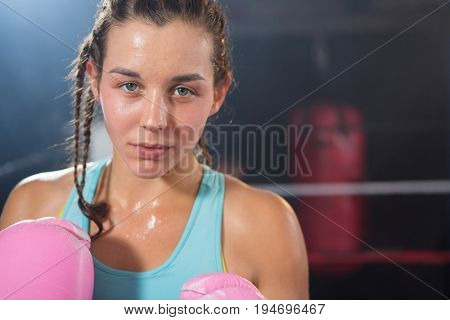 Close-up portrait of young female boxer in boxing ring