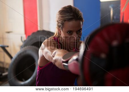 Young female boxer punching mitts at fitness studio