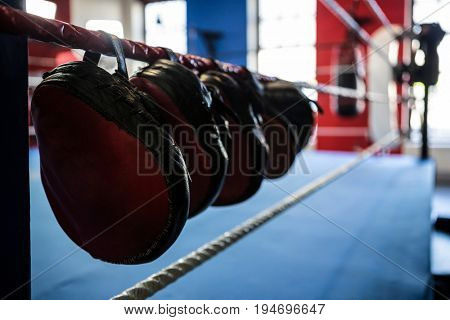 Close-up of mitts hanging from boxing ring at fitness gym