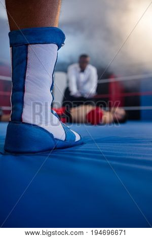 Low section of boxer standing against referee by athlete lying in boxing ring