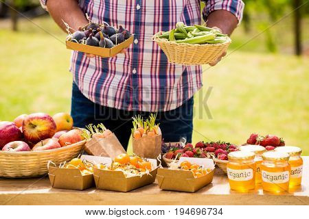 Midsection of man selling figs and okras while standing at farm