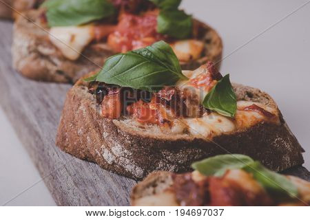 Food. Delicious Bruschettas With Cheese On A Wooden Board