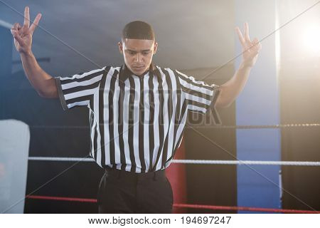 Young male referee gesturing while looking down in boxing ring at fitness studio