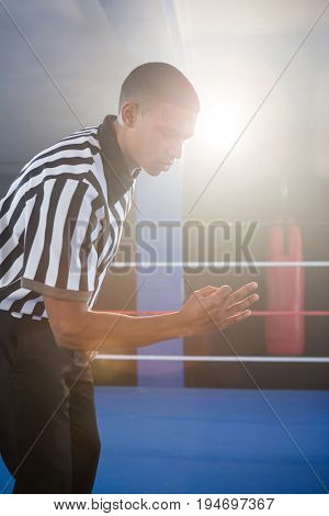 Young male referee gesturing in boxing ring at fitness studio
