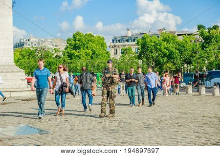 PARIS, FRANCE - JULY 2, 2017: soldier of national Armed Forces of France, keeping security after recent terrorist attacks in Paris. Arc de Triomphe at the center of Place Charles de Gaulle.