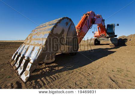 A large orange backhoe parked at a construction site