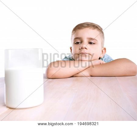 A pretty little child with enormous glass filled with tasteful organic milk. A thoughtful serious small kid with golden hair looks at a big glass of milk from a distance isolated on a white background