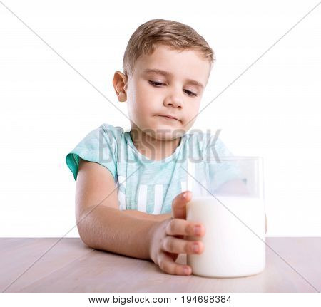 A thoughtful adorable small kid with golden hair in ablue T-shirt holds a transparent glass full of organic tasteful milk and sits next to the classic and wooden table, isolated on a white background.