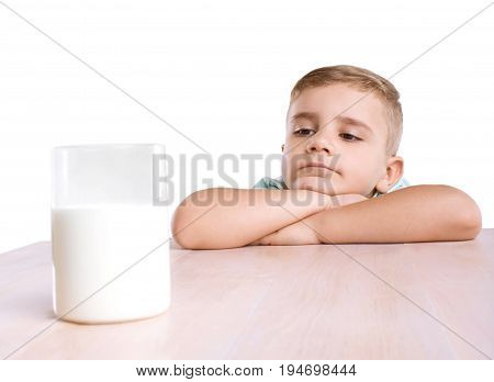 A cute small child in a navy shirt lies on his crossed hands and looks at the transparent glass of tasteful milk in front of him,  on a brown wooden table, isolated on a white background.
