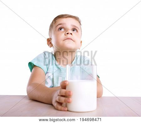 A wonderful little kid with a golden hair sits close to the light brown classic table and holds a glass full of tasteful and white milk, looks very cute, isolated on a white background.