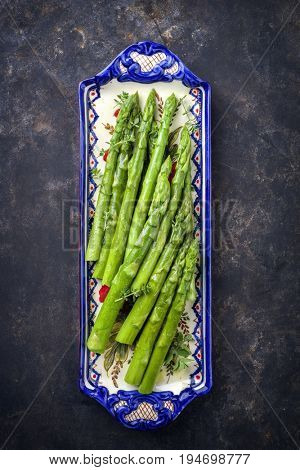 Boiled green Asparagus as close-up on a plate