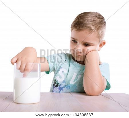 A thoughtful small blonde boy in a bright blue T-shirt is sitting right next to the glass of milk. The cute baby boy is dipping his tiny finger in the organic milk drink, isolated on white background.