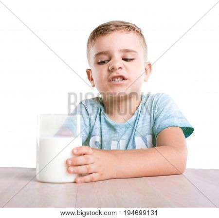 A lovely and adorable little kid is sitting next to the glass of fresh milk. A cute little boy does not want to drink milk, isolated on a white background. Small boy isn't pleased with his glass of a healthful milk.