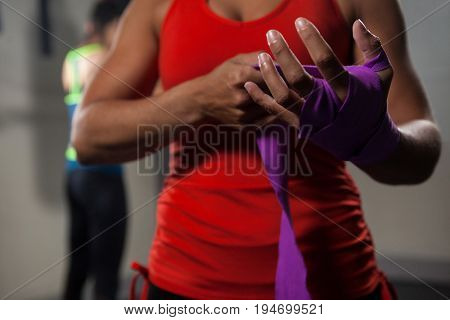 Mid section of woman tying hand wrap on hand in fitness studio