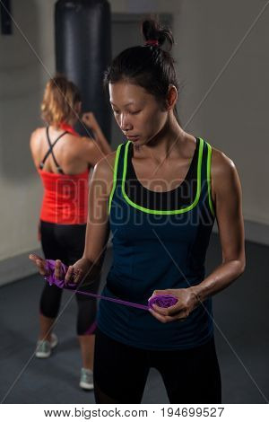 Woman tying hand wrap on hand in fitness studio