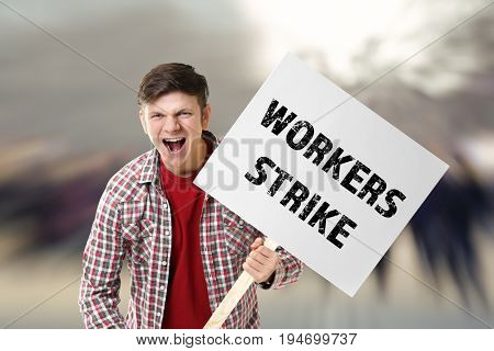 Young man with signboard and blurred crowd on background. Workers strike concept