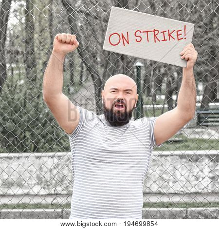 Man with placard on workers strike outdoor