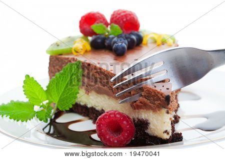 Fork cutting into a double decker chocolate cheese cake, Focus on fork shallow depth of field