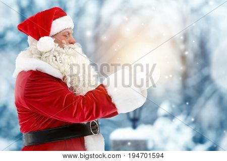 Santa Claus holding magical light in hands on blurred background