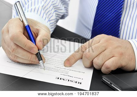 Businessman with pen analyzing resume at desk in the office