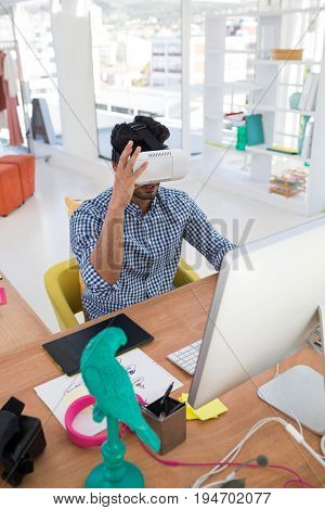 Graphic designer in virtual reality headset working on computer at desk in the office