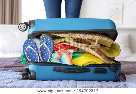 Open heavy suitcase with different personal stuff on bed. Luggage overweight concept
