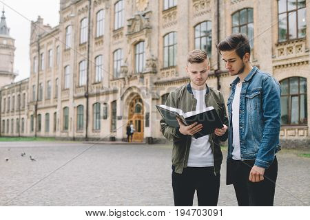 Two handsome and serious students standing in front the university and reading a huge book. They are trying to understand that difficult information. Close up
