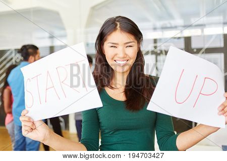 Woman in start-up during creative workshop holding two signs reading