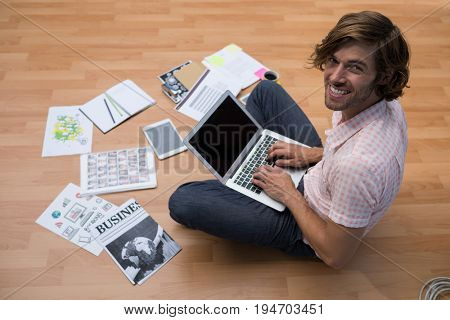 Portrait of male executive using laptop while sitting on floor in the office