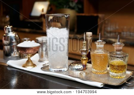 Bitters, infusions and mixing glass with ice on bar counter