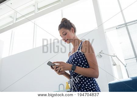 Young female executive using mobile phone in the office