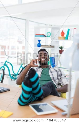 Smiling male executive talking on mobile phone while relaxing at his desk in office