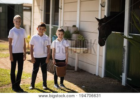 Smiling kids standing with a bucket to feed the horse