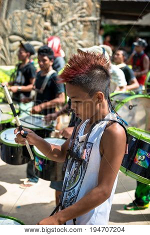 BORACAY, WESTERN VISAYAS, PHILIPPINES - JANUARY 11, 2015: Filipino boy with different hair playing drums at Ati-Atihan Festival at White Beach.