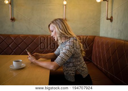 Beautiful woman using mobile phone at table in restaurant