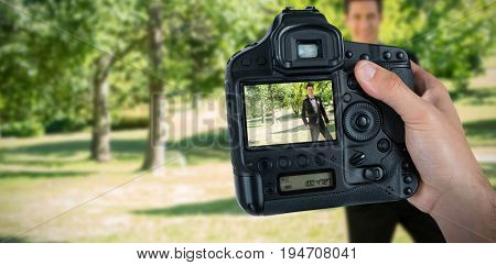 Cropped hand of photographer holding camera  against portrait of handsome bridegroom standing in garden