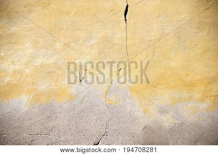The closeup of a yellowed facade with a crack in the wall.