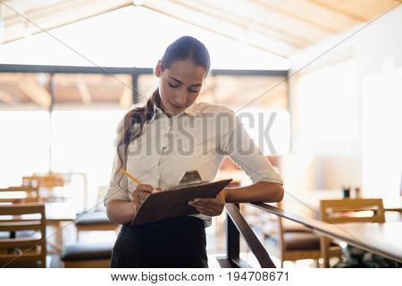 Female bartender writing on clipboard at bar counter