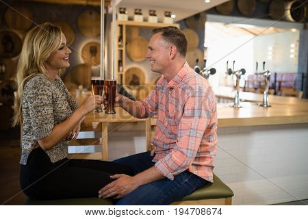 Happy couple interacting while toasting a glass of beer at bar counter