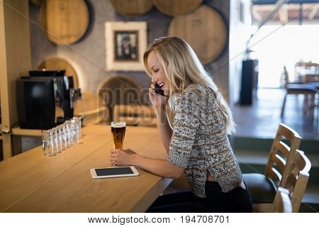 Smiling beautiful woman talking on mobile phone at bar counter
