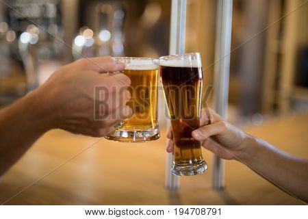 Close-up of couples hand toasting glass of beer at bar counter