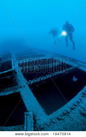 Divers exploring a shipwreck under the sea
